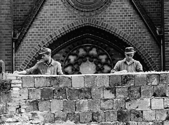 Politics. Germany. The Berlin Wall. pic: 1961. East German workmen reinforce the Berlin Wall by putting glass fragments on top of the brickets.