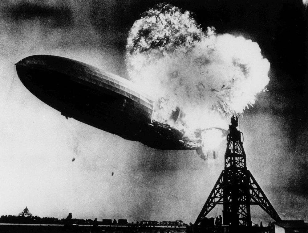 ADVANCE FOR SUNDAY AUG. 22--FILE--This photo, taken during the initial explosion of the Hindenburg, shows the 804-foot German zeppelin just before subsequent explosions sent the ship crashing to the ground at Lakehurst Naval Air Station in Lakehurst, N.J., May 6, 1937. The roaring flames silhouette two men, at right atop the mooring mast, dangerously close to the blasts. The scene stimulated NBC radio broadcaster Herbert Morrison to give a memorable and highly emotion account of the disaster. (AP Photo/Philadelphia Public Ledger, HO)