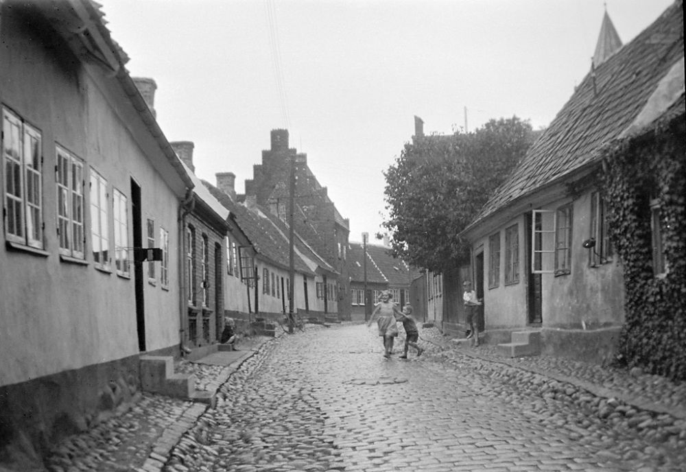 Children in Præstegade street (Priest street) in Kalundborg. In the background to the left is a medieval house with stepped gable roof. 1933