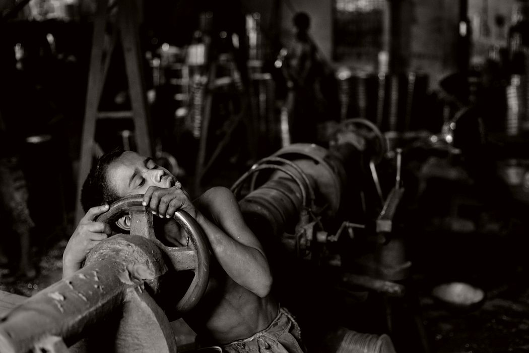 09-  Shakil falls asleep on his tools after hard work at aluminum factory. Aluminum Factory in Chittagong, Bangladesh .