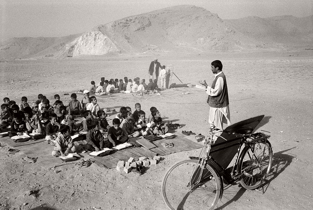 AFGHANISTAN. Tarakhil. Classes are held in the open for lack of space in a village school donated by Japan. The ground had to be demined first.