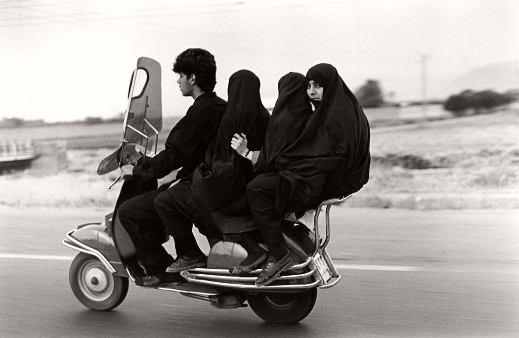 IRAN. Shahr Rey. Young man, three veiled girls in a four-seater motorbike. 1997.