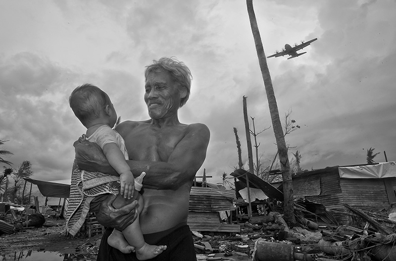 This image shows the quite happy moment in which the rescue planes started to arrive, delivering humanitarian aid sometimes parachuted from the air and beginning to displace the survivors from Tacloban to Cebu City or to Manila.  Remaining as the only two survivors of a family, a grandfather had remained very attached to his granddaughter protecting her throughout the ordeal and as a result of the humanitarian aid he had been able to feed her with some powder milk. Despite that the grandfather had been affected by some minor scratches, the health of both of them was stable. One of the most shocking experiences to observe during the aftermath of the typhoon, was the reaction of the people. Many of them , instead of showing any signs of distress, quite on the opposite they smiled when approached and even laughed when asked about their fate. As I was informed later , that was a way of coping with Post Traumatic Stress Disorder. The magnitude of their losses was so overwhelming that it was just more than a normal human being could bear, so instead of dealing with their sadness at that point they joined other people and tried to keep themselves busy either by cleaning the debris or constructing small in which to live in the short run. As one of the mental health doctors helping them told me, the realistic dimensions of their loss would come to haunt them later, but for the moment it was simply too much.  At some places the children played cheerfully between themselves oblivious to many near cadavers, some of them could have probably been someone from their families.