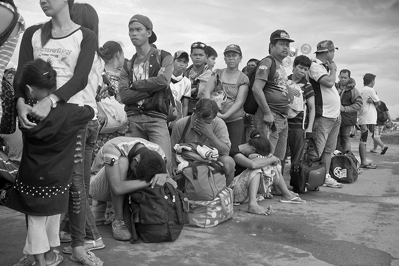 After having waited for days and nights at the devastated airport of Tacloban to be able to get into the flight list destined to an evacuee center in Manila, all the evacuees show deep signs of exhaustion,desperation and disbelief. They had lost part of their families, their homes, their jobs,and the possibility of going to a far away evacuation center offered no future, it became alike living as like a  a refugee in their own country, so thats why many others  chose to stay and have their homes rebuilt out of pieces of debris rather than evacuating to Manila. Having lived a few nights  inside a camping tent at the remainings of the Tacloban airport, I witnessed a living hell; at night it never stopped raining, and even inside the tents everything got totally soaked. The wind never stopped blowing and mixed with the sounds of helicopters and rescue or relief airplanes,it made sleeping an impossible ordeal. Unbelievable enough, the evacuees had to stay waiting outdoors without any type of shelter for many days and nights. Many of them were children, babies, old people, women or people who had been wounded during the typhoon, and in order to not lose their turn in the cue they remained in line waiting, sleeping amongst each other, or on top of their suitcases, suffering in silence.  During the first days of the evacuation many organizations offered them water and food knowing that there were going to be on the news, but when the Tacloban disaster wasnt on the news as much, numerous organizations left the country leaving the evacuees again without food or water. As for lack of shelter  one night a baby died dehydrated, and the mother asked the people to bury her baby around the airport since she had other children and she didnt want to lose her place in the line. From that day some camping tents were disposed for the evacuees.