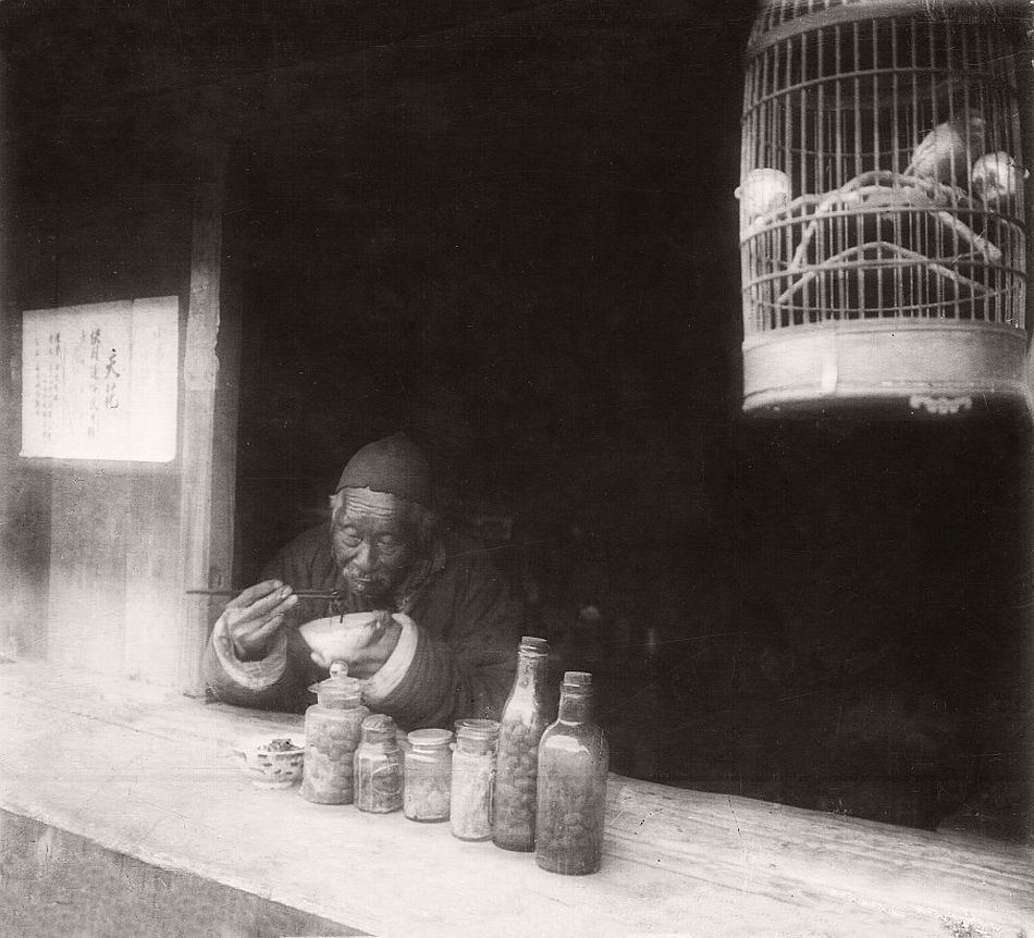 Old man eating noodles in his shop, bird in a cage, Shanghai, 1923