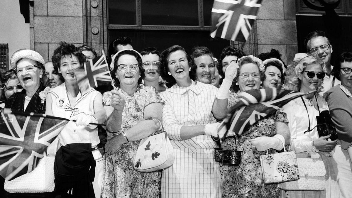 Cy Wolf / Chicago Tribune Flag-waving crowds wait to get a glimpse of Queen Elizabeth II outside the Museum of Science and Industry on July 6, 1959.