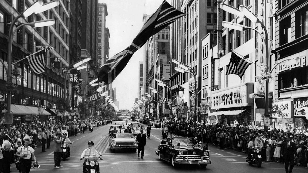 Chicago Tribune historical photo A limousine carrying Queen Elizabeth II passes beneath a huge British flag hanging above State Street while en route to the Drake Hotel in Chicago on July 6, 1959.