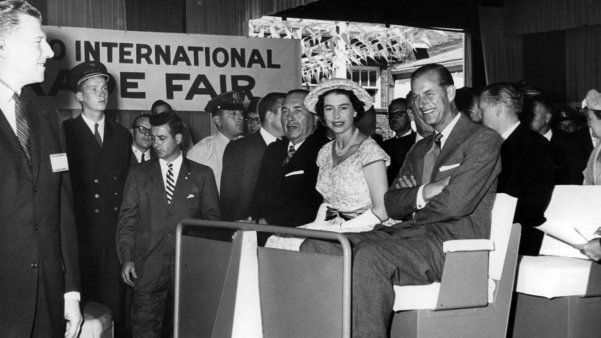 Chicago Tribune historical photo Queen Elizabeth II sits between Mayor Richard J. Daley, left, and Prince Philip as they ride in a cart at Navy Pier while touring the Chicago International Trade Fair on July 6, 1959.