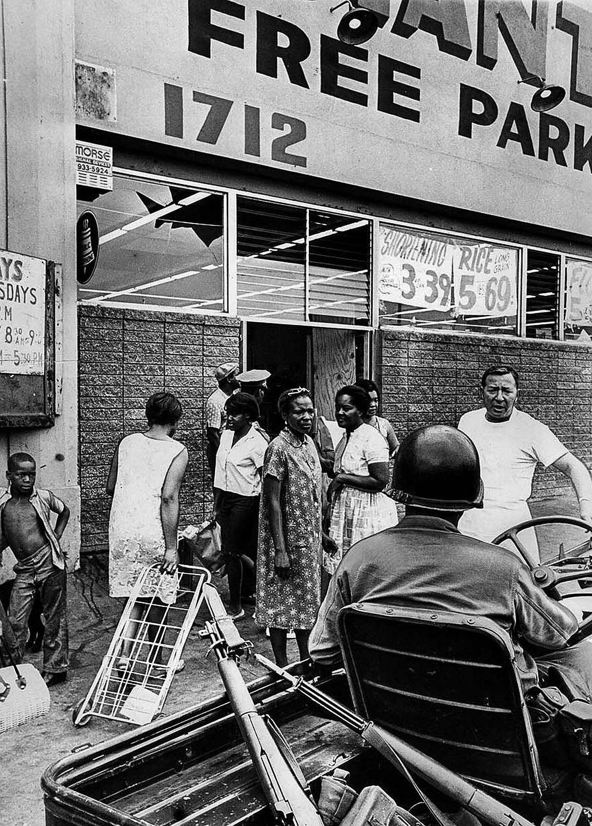 Aug. 16, 1965: Only women were allowed to enter the Giant Food Market at 1712 E. 103rd St. after it reopened during Watts Riots. Clerks were wearning guns. Man facing camera is manager Carl Margolis.