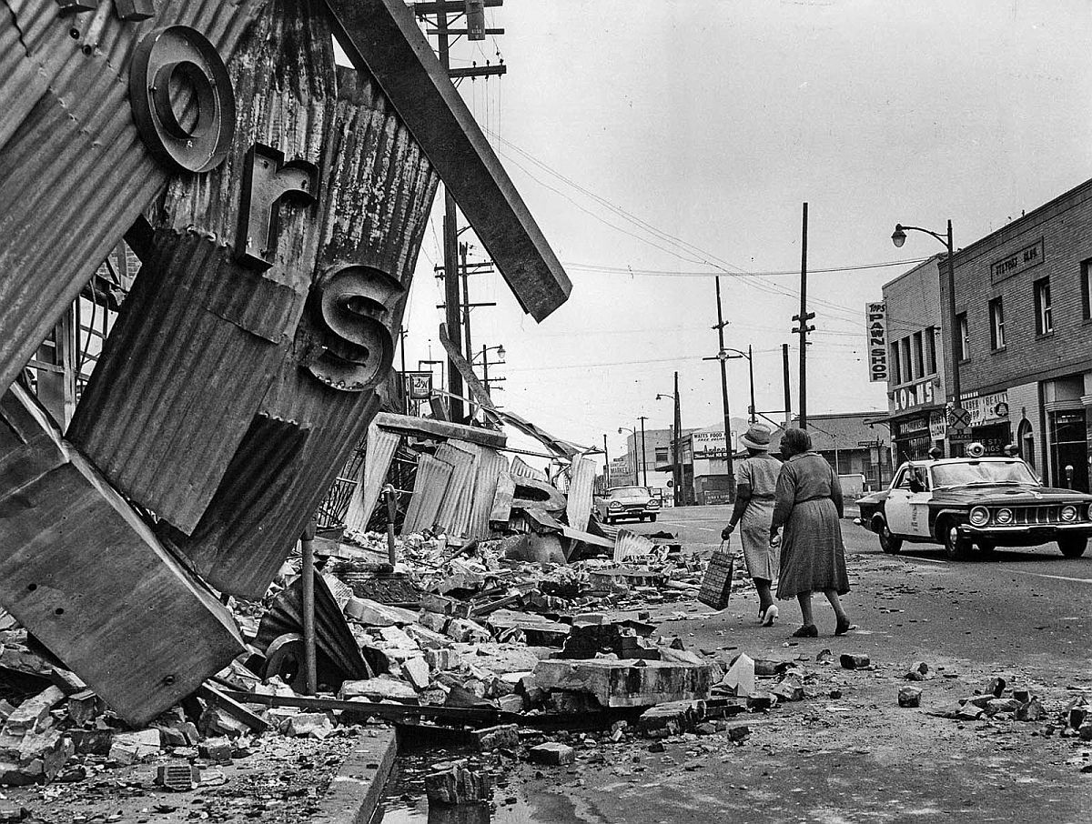 Aug. 16, 1965: Two women walk around the ruins of store on 103rd St. near Maie Ave. in the center of the riot area.