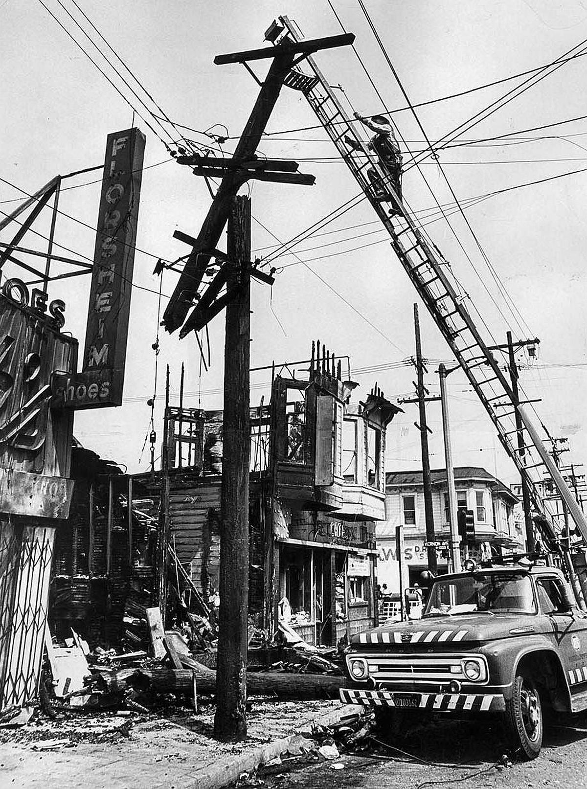 Aug. 17, 1965: Dept. of Water and Power lineman works among wires on poles burned and snapped apart by store fires at Central Ave. at Vernon.
