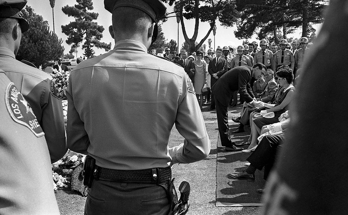 Aug. 17, 1965: Mrs. Ronald E. Ludlow, widow of deputy sheriff killed in rioting, receives condolence from Rev. Lawrence Keene of Crenshaw Christian Church at Inglewood Park Cemetery as Ludlow's fellow officers form an honor guard for fallen comrade.