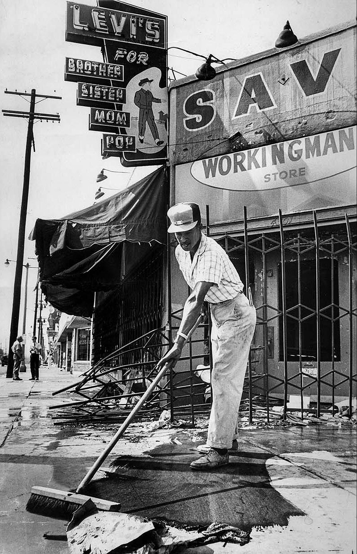 Aug. 17, 1965: Charles Vance sweeps up the litter in front of stores at 45th St. and Central Ave. following the Watts Riots.