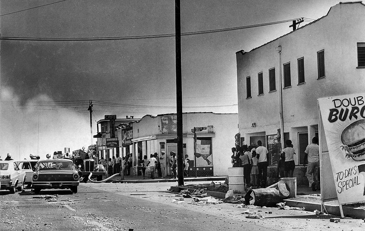 Aug. 13, 1965: Debis litters Avalon Blvd. near 105th St. as crowd watches smoke rise from a building at 108th St.