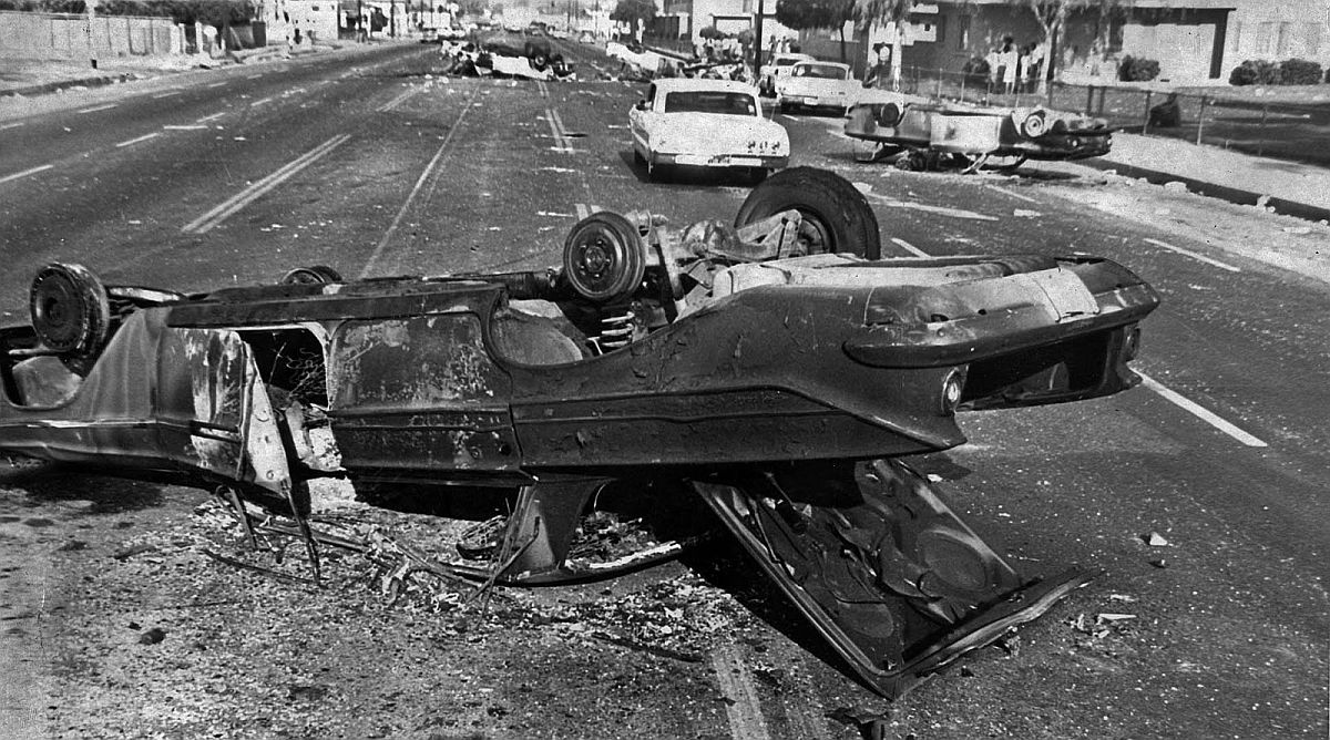 Aug. 13, 1965: A burned car and four others overturned by rioters clog Imperial Highway near Avalon during Watts Riots.