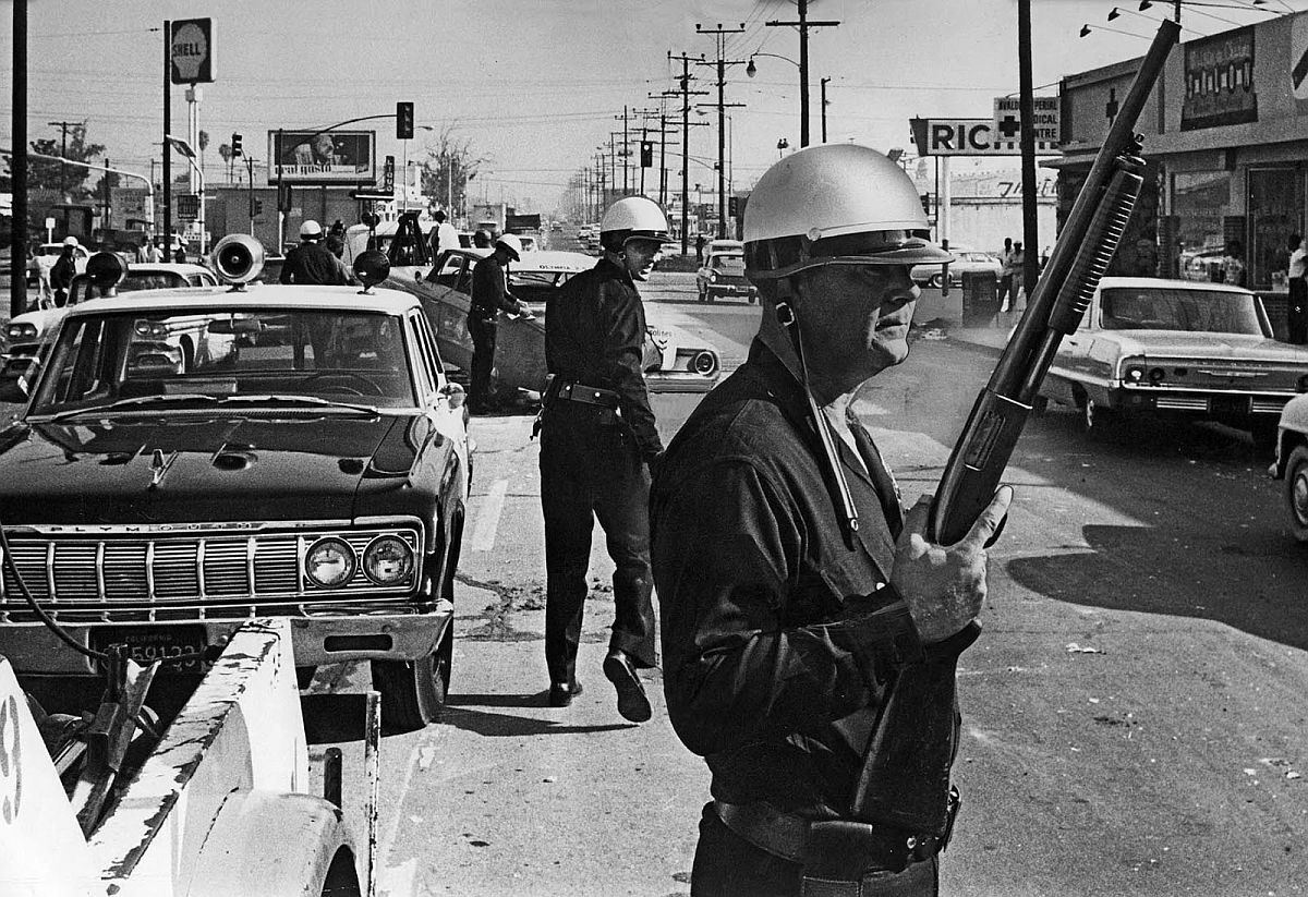 Aug. 13, 1965: Los Angeles police officers stand guard as debris of day of violence is cleared from the intersection of Avalon Blvd., and Imperial Highway, one of the worst trouble spots from which violence was spreading.