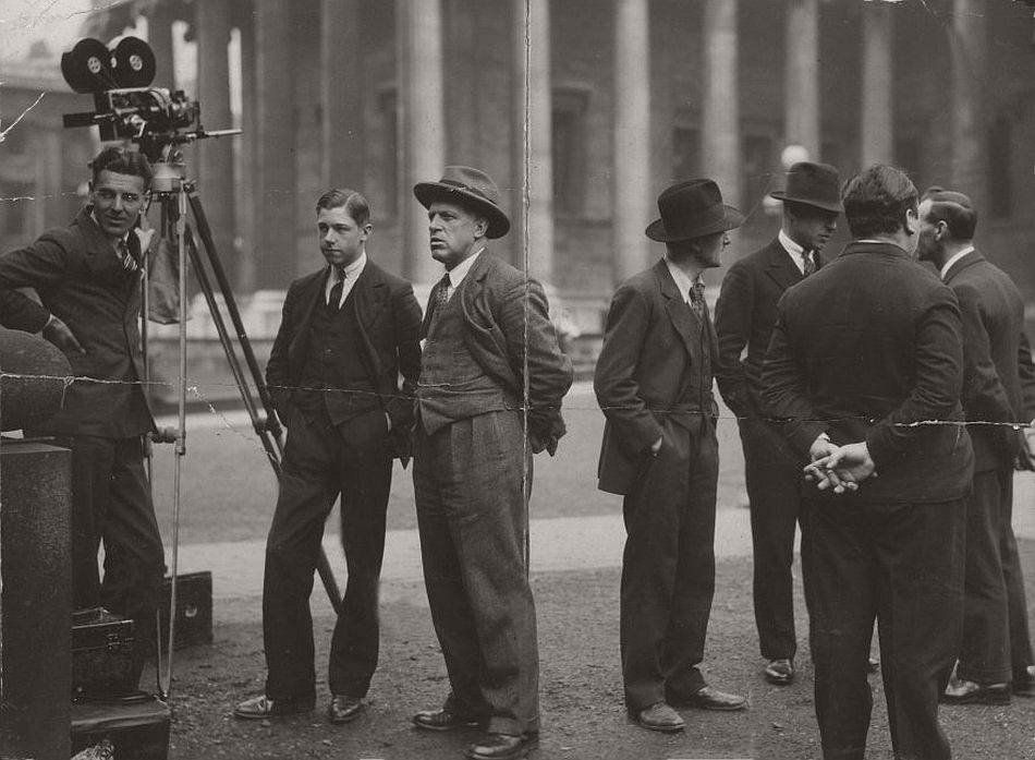 This is a rare picture of Hitchcock on location at the British Museum with cameraman Jack Cox, shot outside as blackmailer Tracy (Donald Calthrop) tries to evade the police by running into the museum. Hitchcock didn't have permission to film inside the museum so reconstructed it with special effects. Although he has his back to the camera, the director is clearly recognisable.