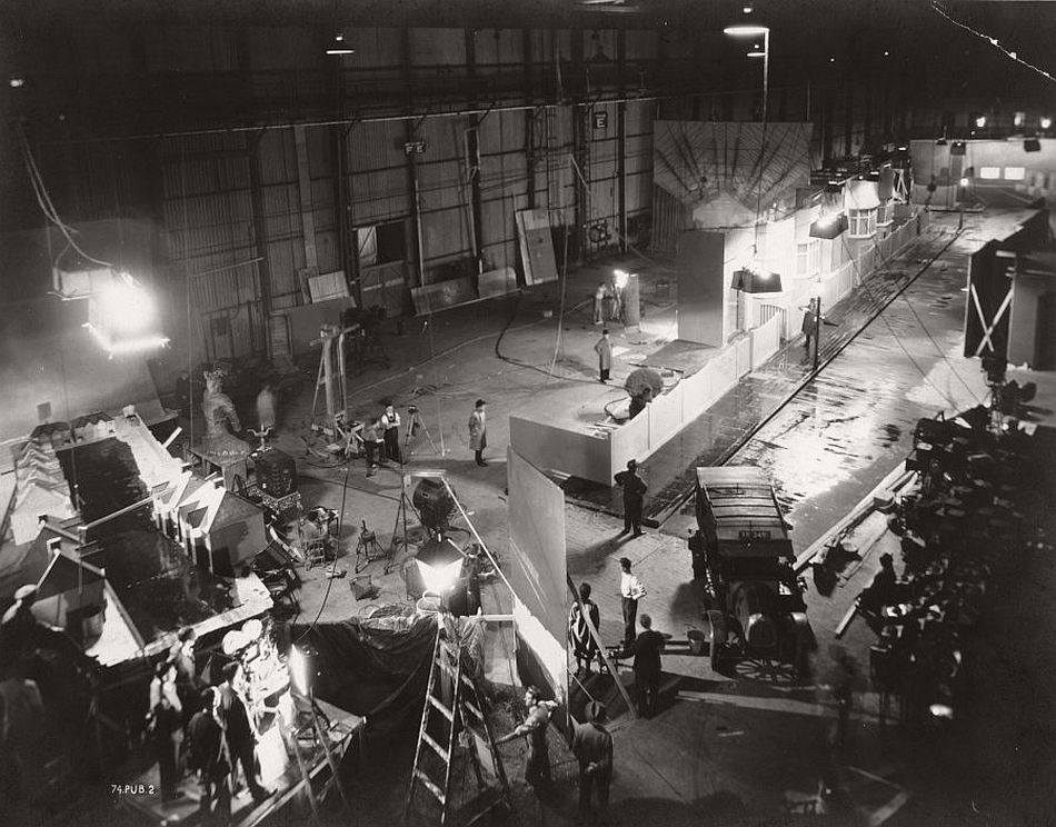 This is the large street set for the opening scenes of Rich and Strange (1931), in which the character of Fred (Henry Kendall) is seen leaving his humdrum job and returning to his suburban home. Spot the tiny but again unmistakable figure of Hitchcock with his hands on his hips surveying the set in the centre of the image.