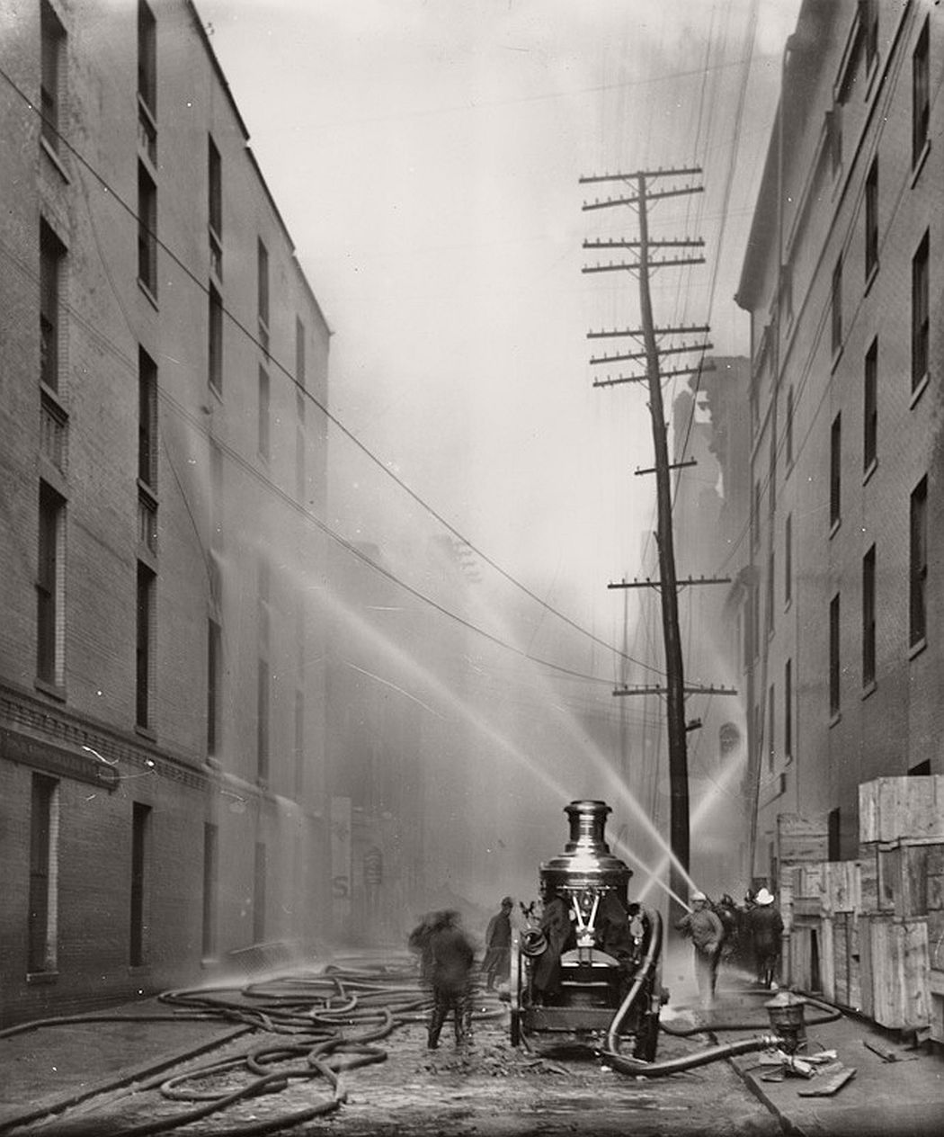 Firefighters spraying water on buildings along German St. during 1904 fire