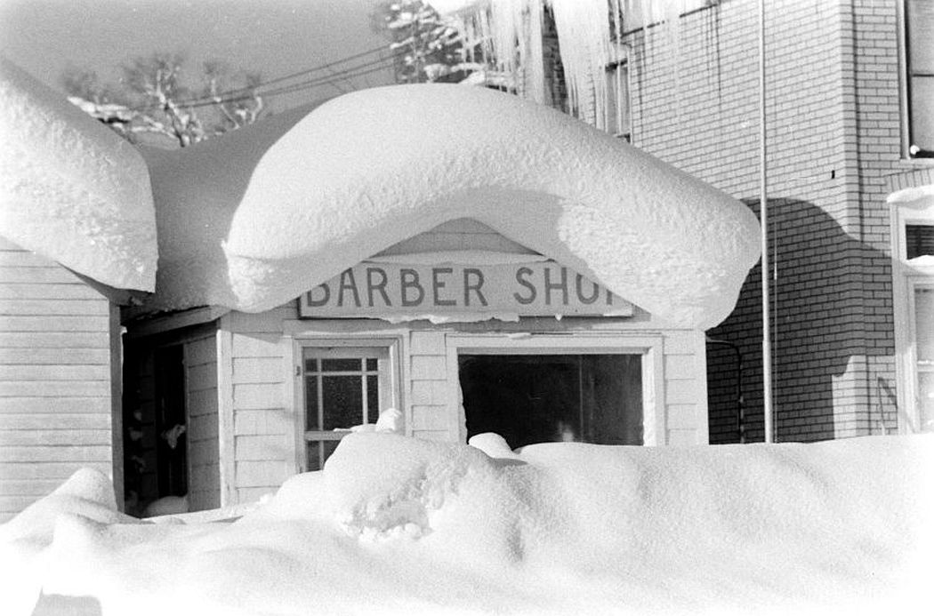 A local barber shop peeks out from behind six feet of snow.