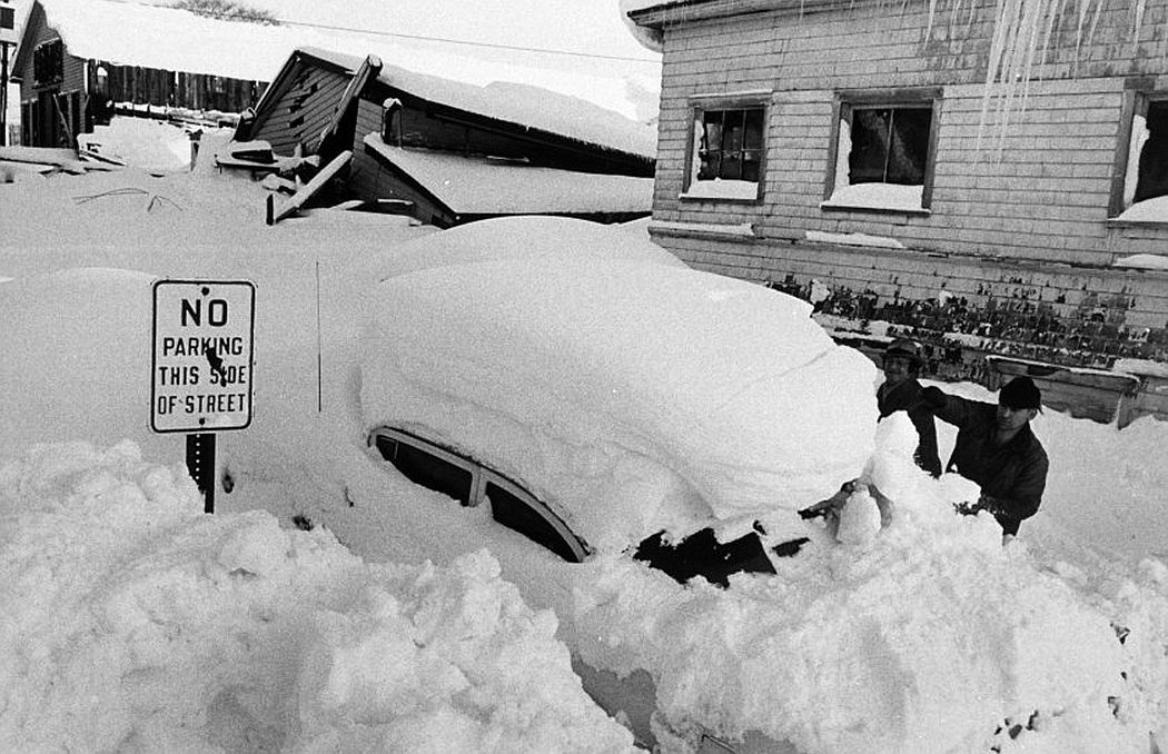 Men attempt to dig out a buried car.