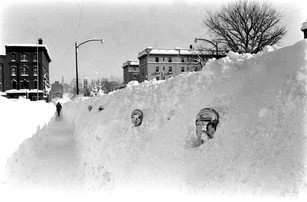 Parking meters peek out from within a snowbank in Oswego, New York, 1958.