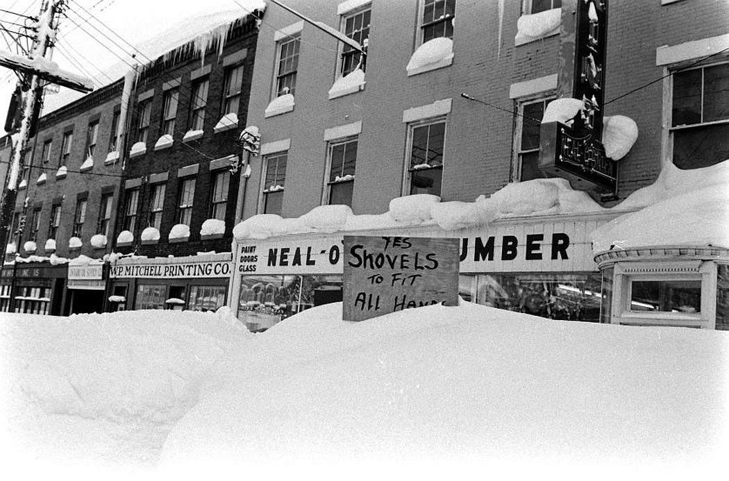 A handmade sign advertising shovels is partially obscured by snow.