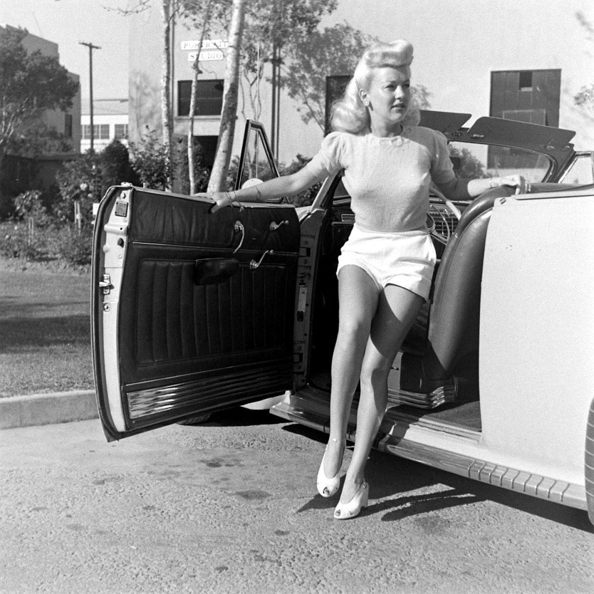 """Going to studio in the morning, Betty steps into roadster. Once asked to comment on her hips, well displayed here, she said, """"They're just where my legs hook on."""""""