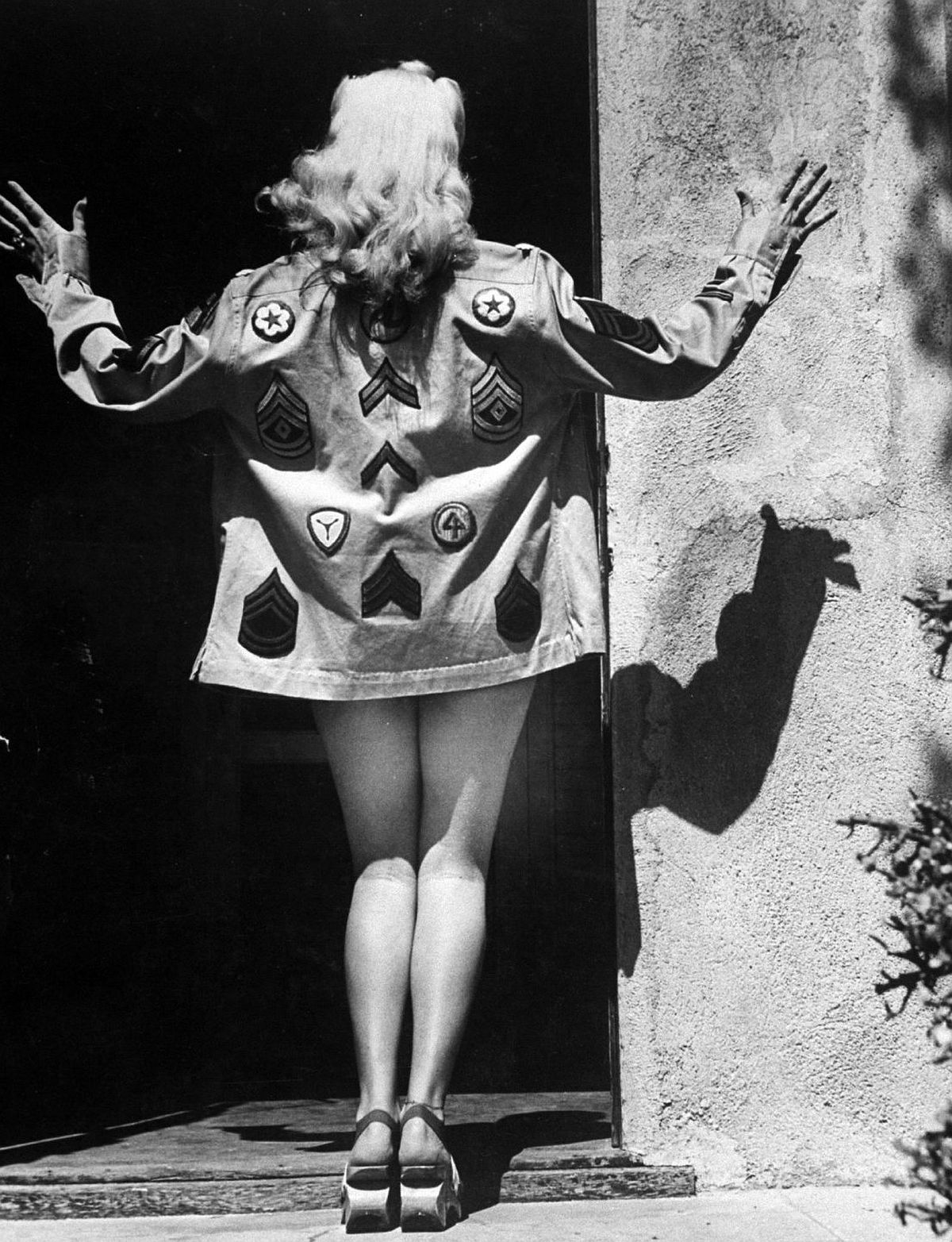 Betty models a coat of her own design which features decorations of Army corps and rank insignia. Betty is one of the biggest pin-up favorites of servicemen everywhere.