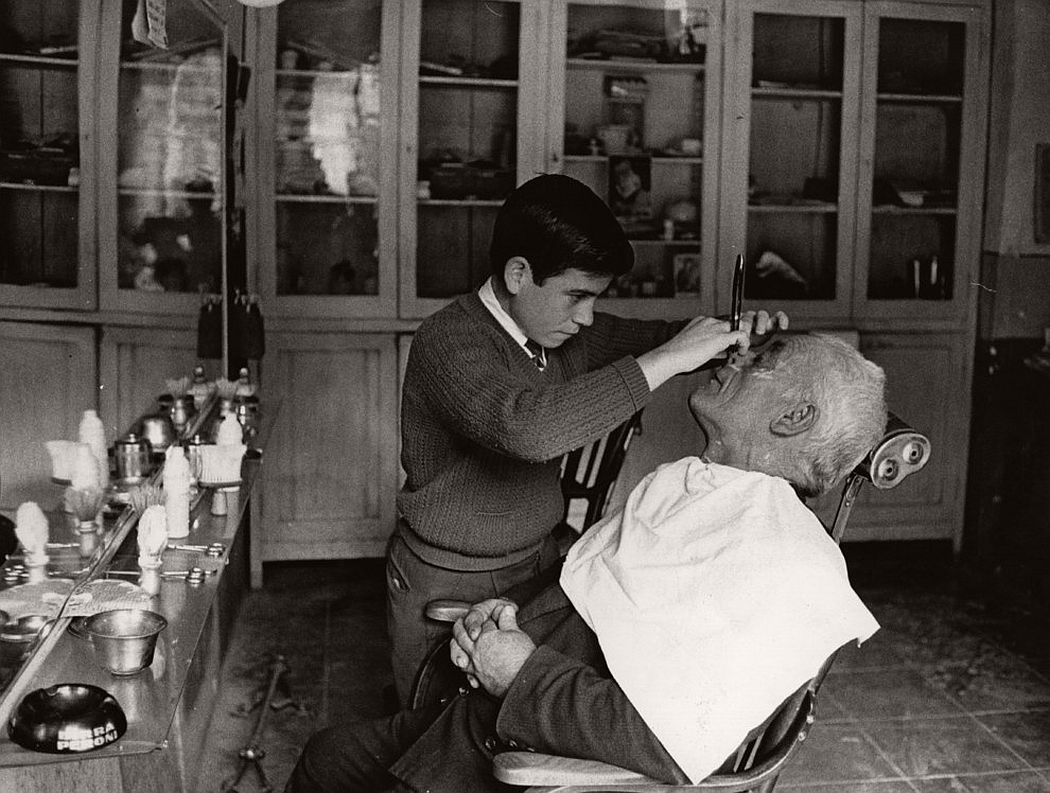 A young barber at work on an elderly client in Italy. 1955. (Keystone / Getty Images)