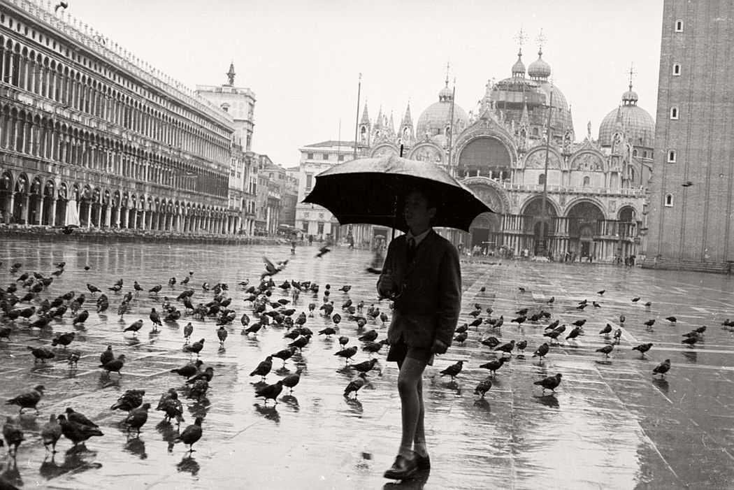 A schoolboy walks through the rain in Saint Mark's Square, Venice. March 1958. (Koenig/BIPs / Getty Images)