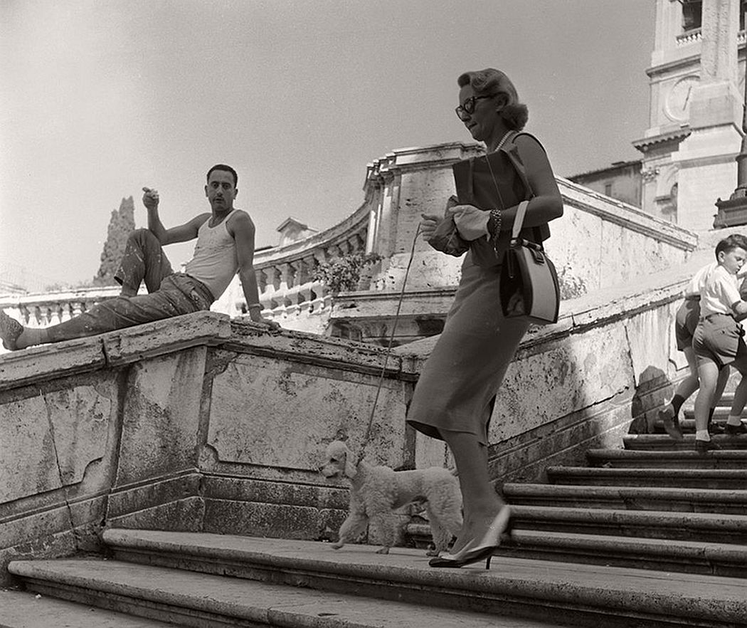 An Italian man watches an American tourist walking her poodle down the Spanish Steps in Rome. Circa 1955. (Evans/Three Lions / Getty Images)