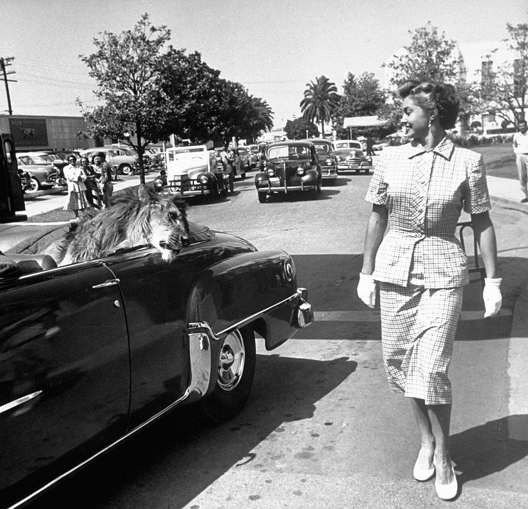 From a chauffer-driven convertible Fagan trades glances with fellow M-G-M star Esther Williams.