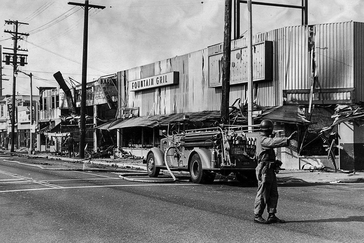 Aug. 15, 1965: Fire truck and national guardsmen stand on scene of desolation on S. Central Ave. following a series of first set during the Watts Riots.