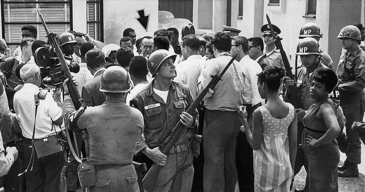 Aug. 15, 1965: Local residents and newsmen converge on California Governor Pat Brown, arrow, as he arrives at Jacob Riis High School in Watts Riot area to have lunch with high-ranking National Guard Officers.