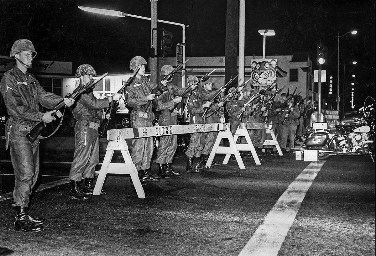 Aug. 15, 1965: National guardsmen, with bayonet fixed, take up position at Atlantic Blvd. and Anaheim St., Long Beach to enforce curfew order. The Watts Riots violence spilled over into Long Beach.
