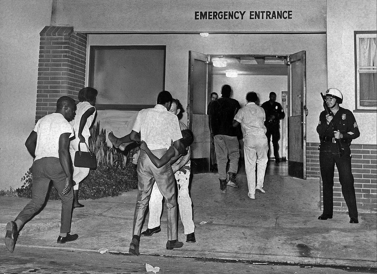 Aug. 13, 1965: A girl injured in Watts Riots is carried into emergency entrance at Oak Park Hospital.