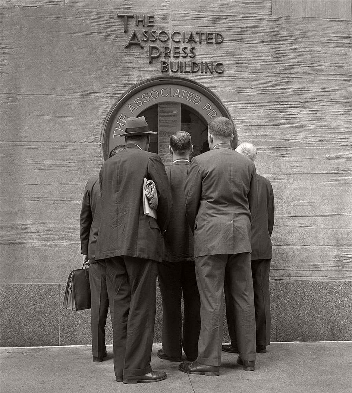 A group of businessmen huddle together at the window of the Associated Press office at Rockefeller Center to read the latest news, 1955.