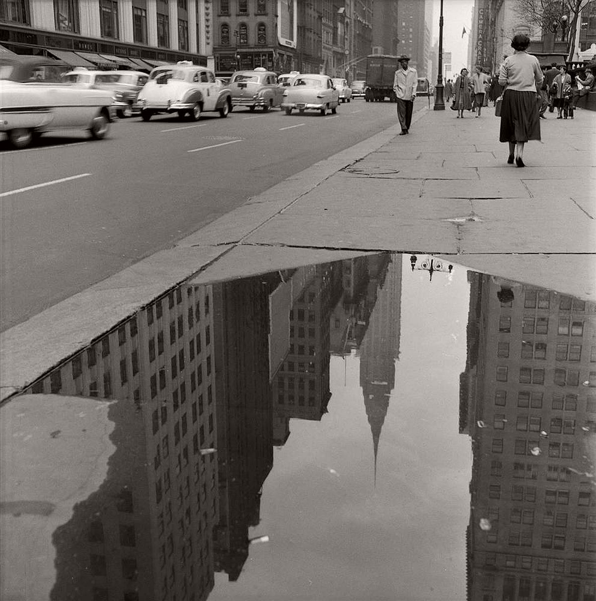 The Chrysler Building is reflected in a sidewalk puddle on 42nd St. in April 1954.