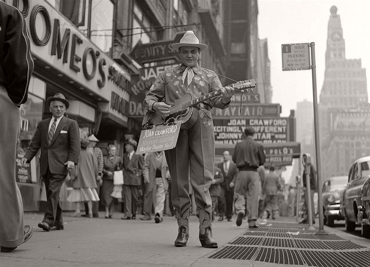 "A street performer promotes the film ""Johnny Guitar"" on the sidewalks of Times Square in Spring, 1954."