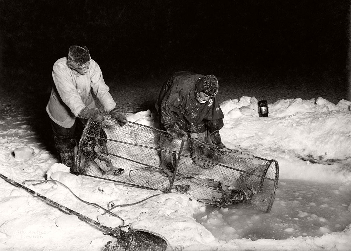 "Expedition cook Thomas Clissold and surgeon Edward Atkinson (right) haul up a seal-baited fish trap during Antarctica's winter darkness.  The team's nearly three years of scientific experiments—particularly in meteorology and geology—laid the groundwork for what is known about the continent today, Jones said.  In addition to their drive to reach the Pole, he said, Scott and his men ""were also driven by a passion to discover more about the world."""
