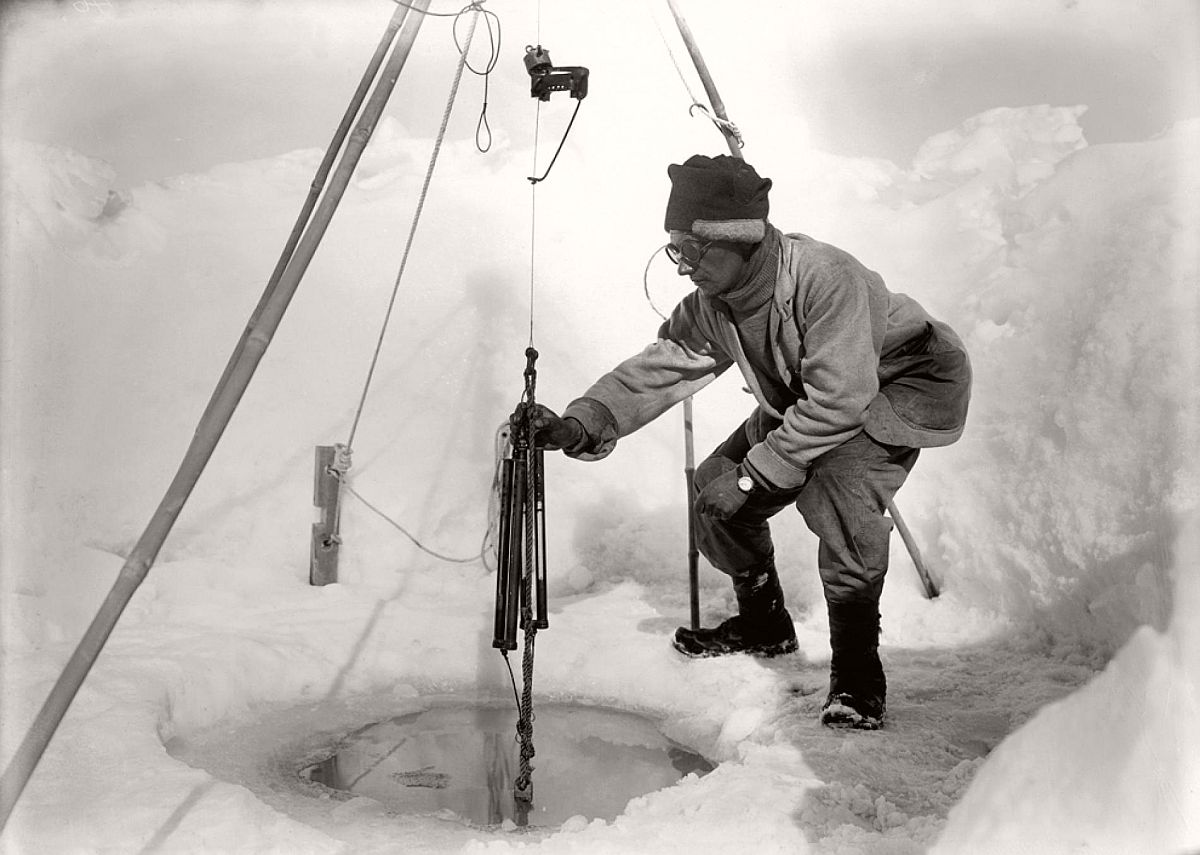 Biologist Edward Nelson tends to a scientific experiment in an ice hole on December 24, 1911.  Terra Nova biologists were fascinated by the bevy of unusual creatures around them, from leopard seals—which they called sea leopards—to killer whales to Adélie penguins.
