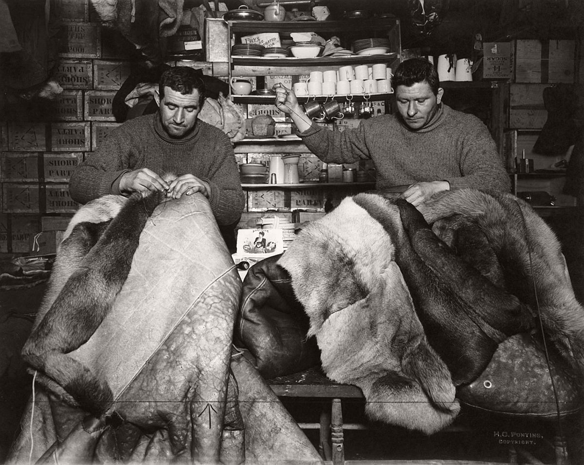 Expedition members repair reindeer-fur sleeping bags inside the Terra Nova hut on May 16, 1911.  For the South Pole journey, the men wore warm, reindeer-fur boots called finneskos, oversize reindeer-fur mitts, and goggles to prevent snow-blindness.