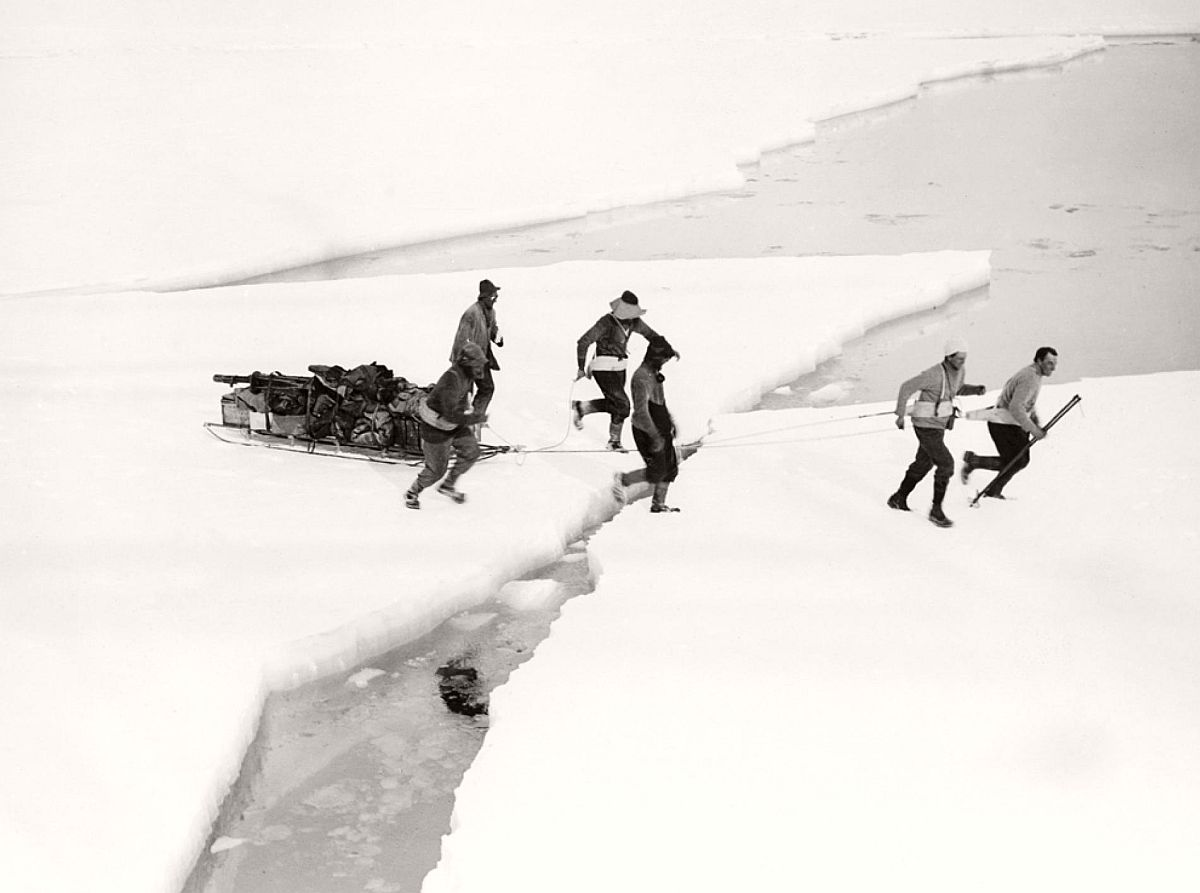 "Members of the western geological party haul a sledge across sea ice in 1911.  The team, led by geologist T. Griffith Taylor, was the first to explore Antarctica's Western Mountains—in Scott's words, a ""vision of mountain scenery that can have few rivals."""