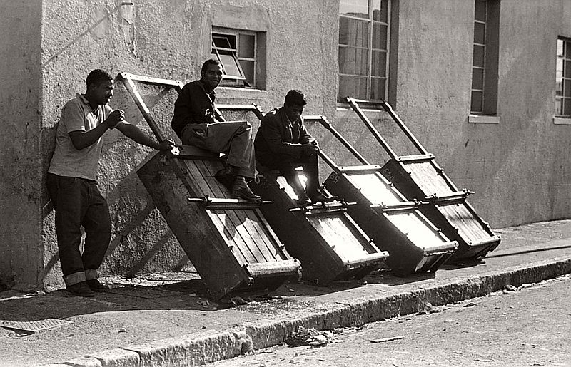 Hawkers' barrows, District Six Hawking fresh vegetables, fruit, or fish, was big business in the area, and beyond. When not in use, hawkers' barrows were stashed along pavements. The wheels were removed to prevent unauthorised use or theft by rivals, District Six, Cape Town, South Africa.