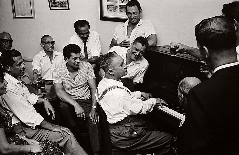 Men socialising around the piano, District Six, Cape Town, South Africa.
