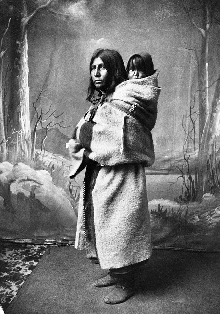 Blackfoot woman and baby on her back, 1886