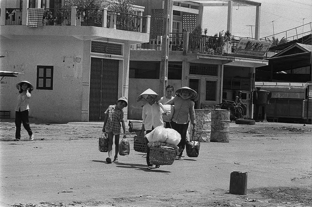Women leaving the area with belongings during street fighting, Saigon, 1968