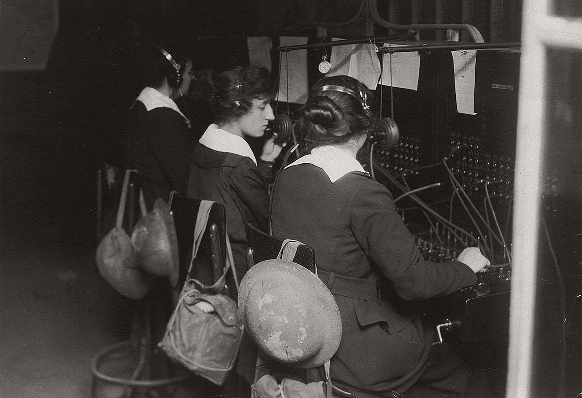 U.S. Signal Corps telephone operators in Advance Sector, 3 km from the trenches in France. The women were part of the Signal Corps Female Telephone Operators Unit and were also known as Hello Girls. Women have helmets and gas masks in bags on back of chairs. # National World War I Museum, Kansas City, Missouri, USA