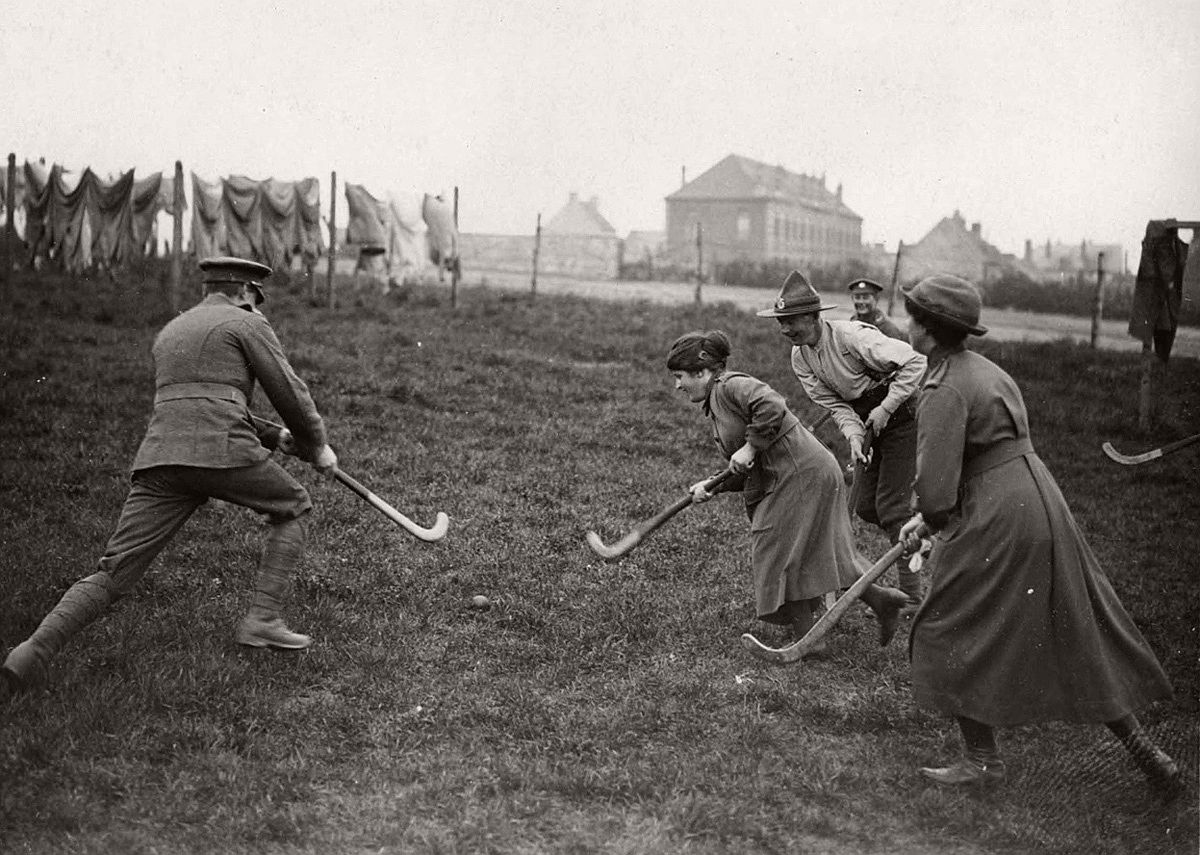 Women's Army Auxiliary Corps (W.A.A.C.) members play field hockey with soldiers in France, during World War I, drying greens and convalescent home buildings visible in the background. # National Library of Scotland